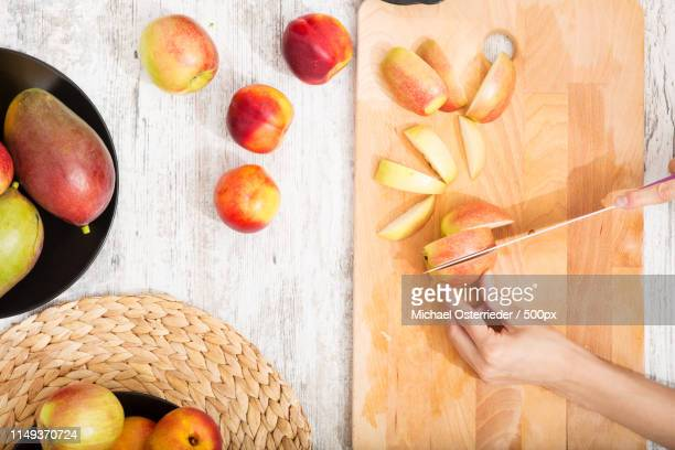 cutting apple while getting online information about nutrition - domestic life imagens e fotografias de stock