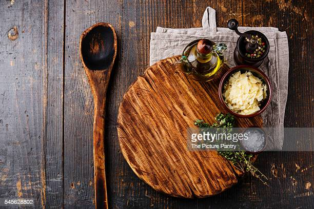 Cutting board, old wooden spoon, seasonings and parmesan cheese on dark wooden background