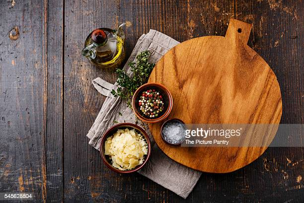 Cutting board, seasonings and parmesan cheese on dark wooden background