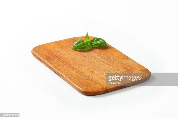cutting board with a basil sprig - bamboo instrument stock photos and pictures