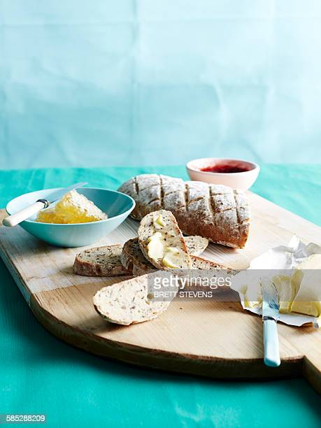 Cutting board with fresh unkneaded bread with honey, butter and jam