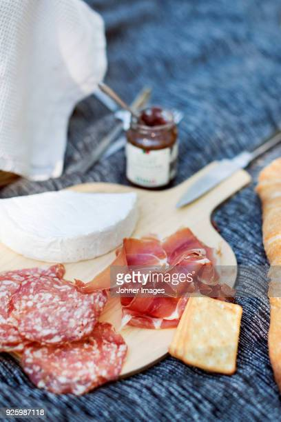 Cutting board with ham, cheese and crackers on table