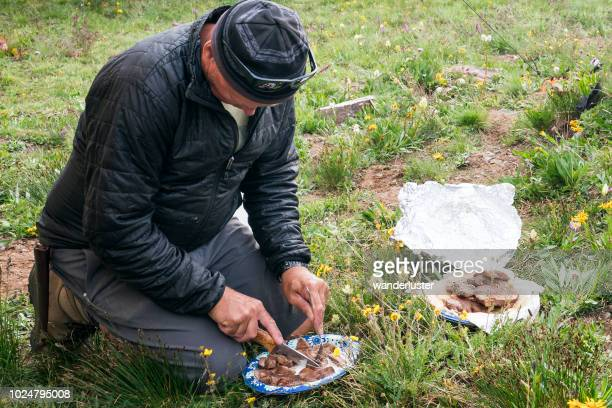 Cutting grilled meat in the grass