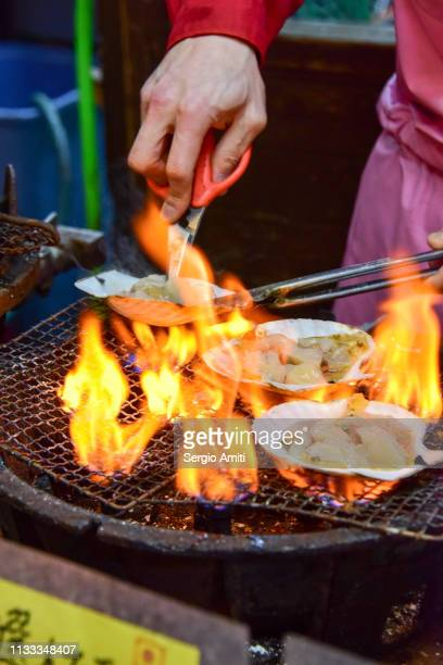 Cutting Hokkaido scallops on a grill with flames