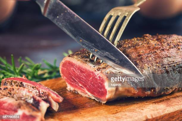 cutting juicy beef steak - red meat stock pictures, royalty-free photos & images