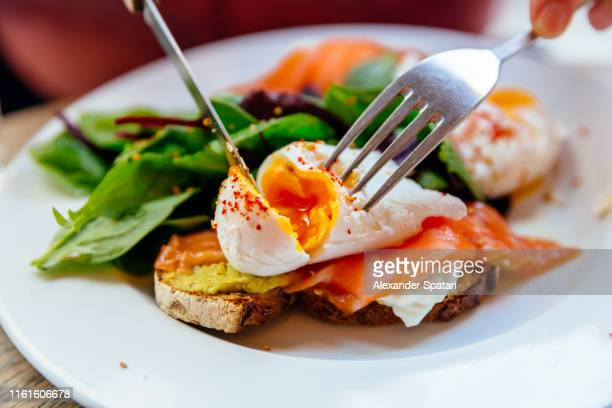 cutting poached egg on top of avocado toast with salmon - たんぱく質 ストックフォトと画像