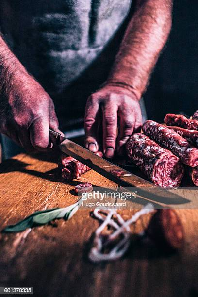Cutting sausage in authentic setting