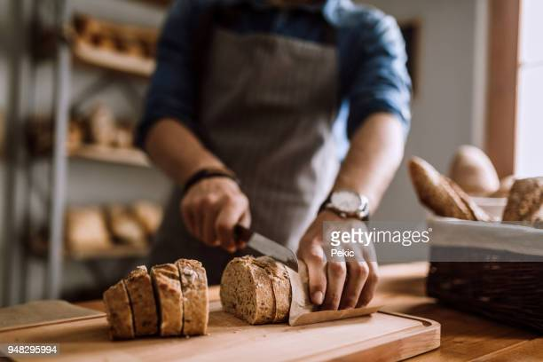 cutting slices of delicious bread - gluten free bread stock pictures, royalty-free photos & images