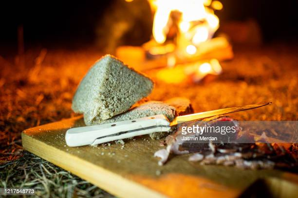 cutting smoked meat and homemade bread near camping fire in night - 薪 ストックフォトと画像