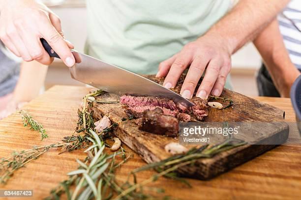 Cutting steak on chopping board
