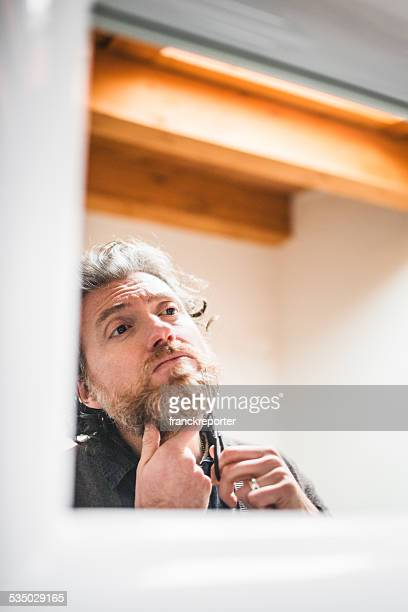 cutting the beard in front of mirror