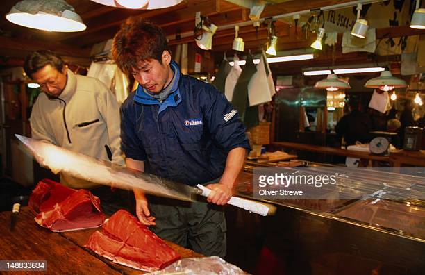 Cutting up a whole tuna, and a few fingers, at the Tsukiji Fish Market in Tokyo- Japan