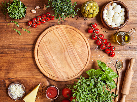 Cutting wooden board with traditional pizza preparation ingridients: mozzarella, tomatoes sauce, basil, olive oil, cheese, spices. 670702624