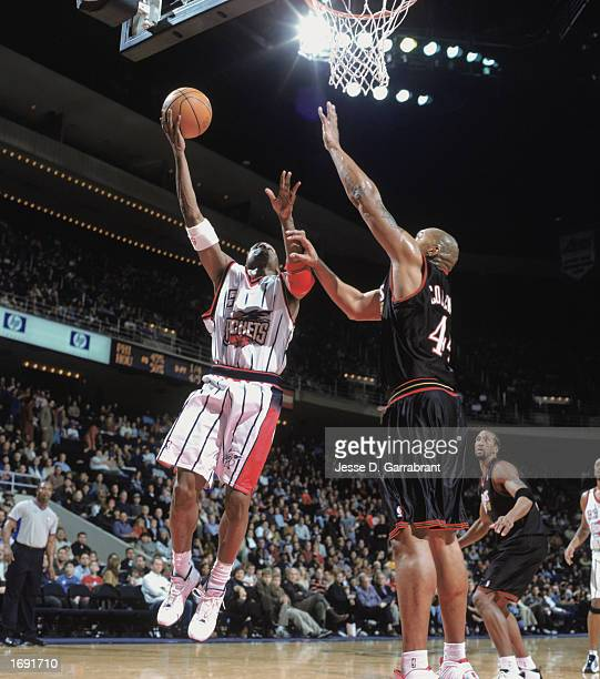 Cuttino Mobley of the Houston Rockets makes a layup against Derrick Coleman of the Philadelphia 76ers at COMPAC Center on December 7, 2002 in...