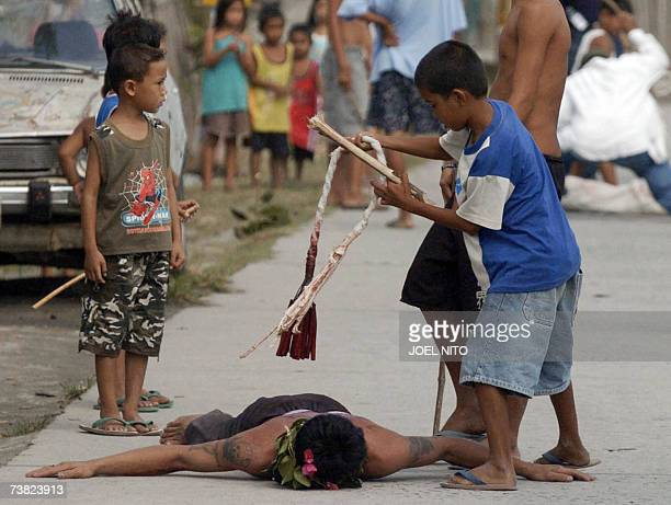 A young boy flagellates a devotee during Good Friday ritual in the village of Cutud north of Manila 06 April 2007 While frowned upon by the Roman...