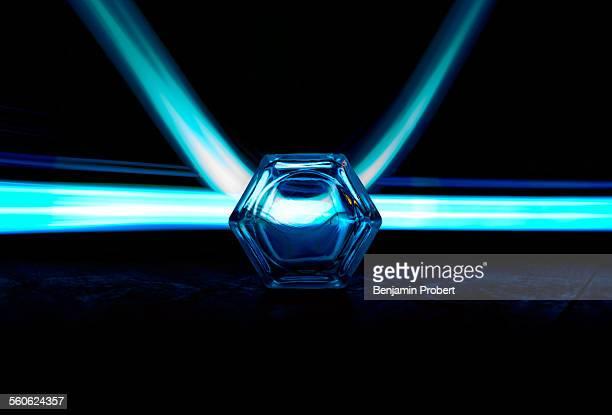 Cyan light streaks through hexagonal glass lens