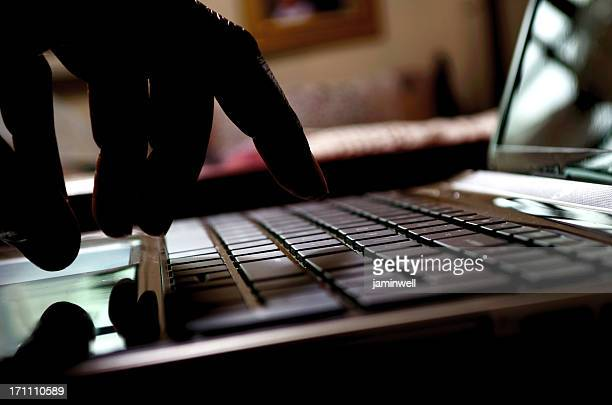 cyber crime hacker typing on laptop