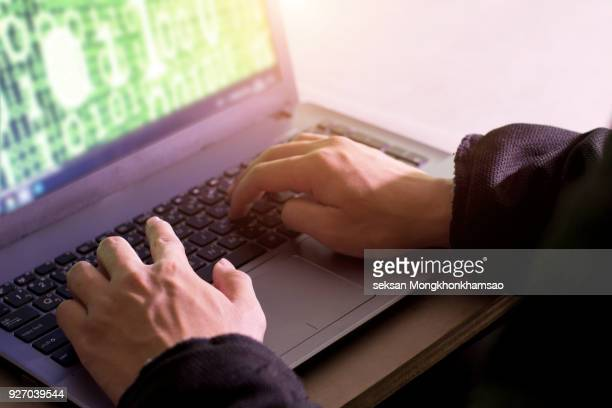 cyber crime hand reaching out through laptop computer and attack signifying in internet theft while using online banking, payment security concept - scammer stock pictures, royalty-free photos & images