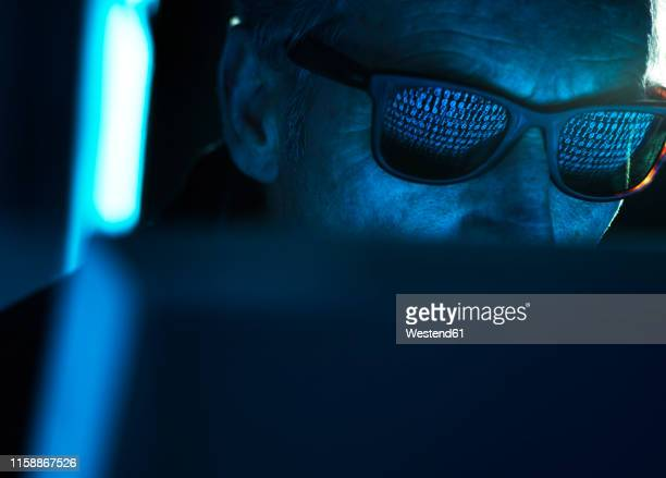 cyber crime, reflection in spectacles of virus hacking a computer, close up of face - identity theft stock pictures, royalty-free photos & images