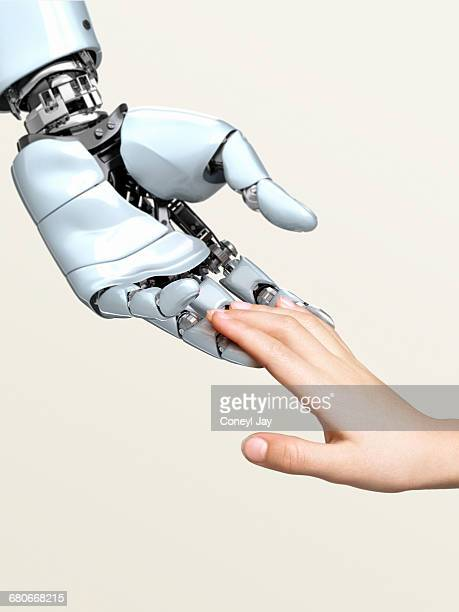 Cybernetic robot and young child's hand touching