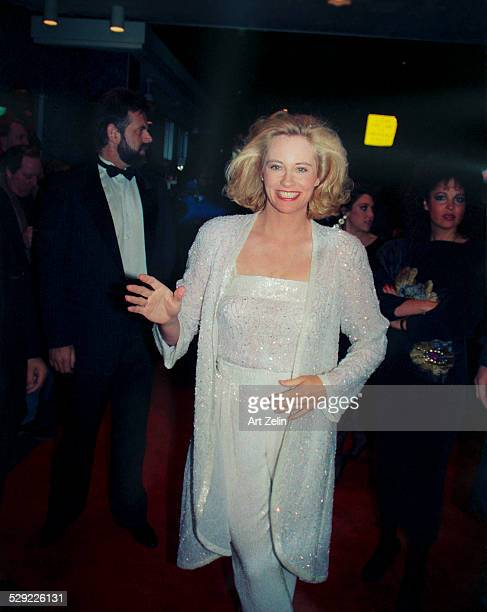 Cybill Shepherd dancing down the red carpet in a white sequined pants suit circa 1990 New York
