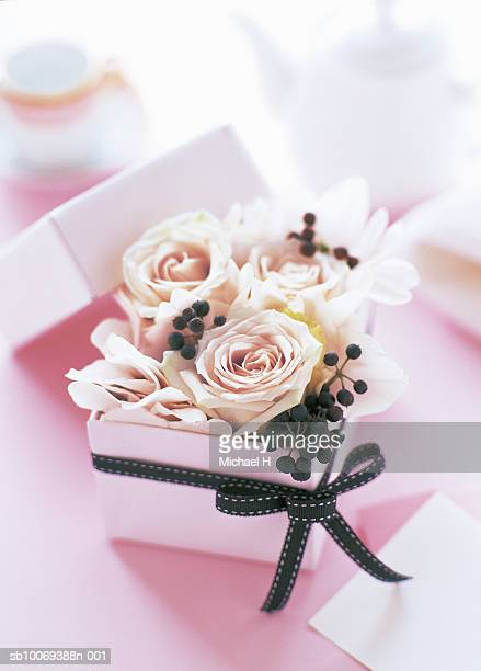 Cyclamen rose and hedera berry arranged in pink gift box with black ribbon
