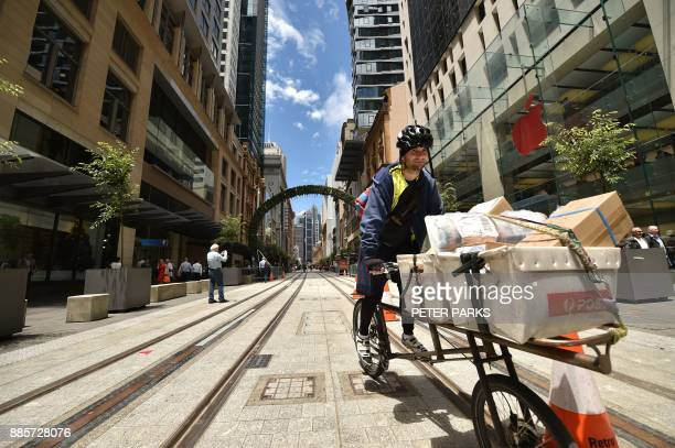 A cycle courier rides down a finished section of George Street where the government is building a light railway system in the central business...
