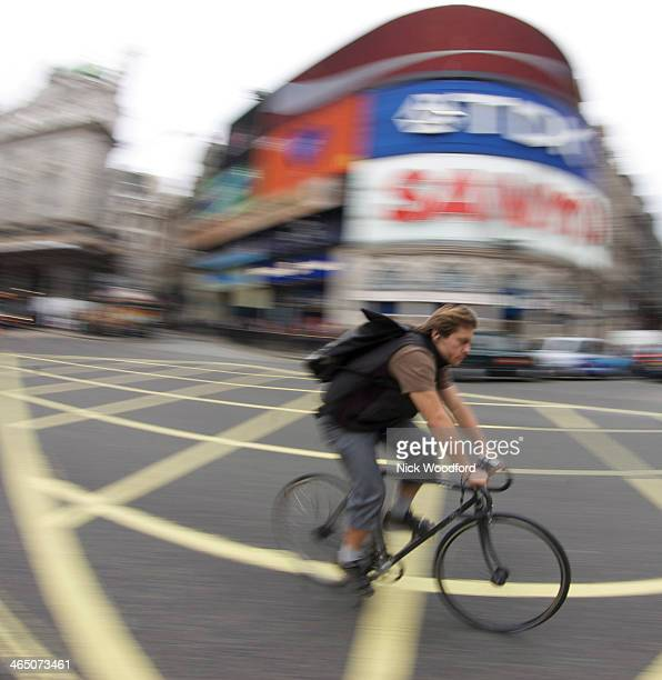 CONTENT] cycle courier speeding over yellow box junction through Piccadilly Circus London in front of the TDK and SANYO advertising