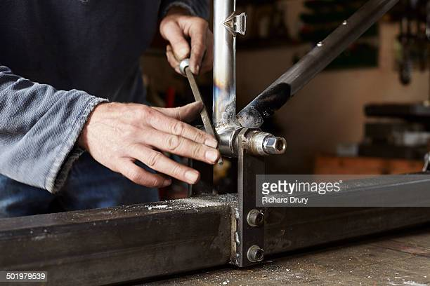 cycle maker preparing frame for chainstay fitting - richard drury stock pictures, royalty-free photos & images