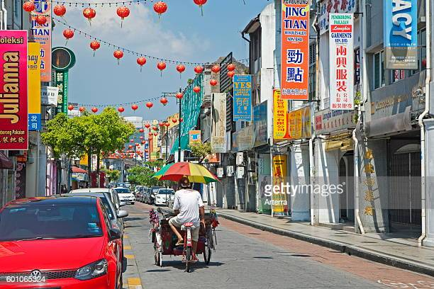 Cycle rickshaw / beca with umbrella riding through shopping street in the city George Town / Georgetown Penang Malaysia