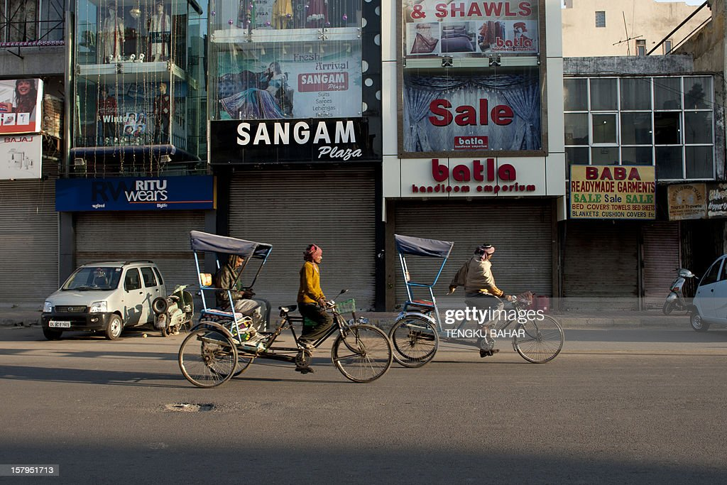 Cycle rickshaw pullers ride past retail shops at a market in New Delhi on December 8, 2012. India has long been criticised as one Asia's most inefficient bureaucracies, with its byzantine regulations and widespread corruption seen as a major deterrent to foreign investment.