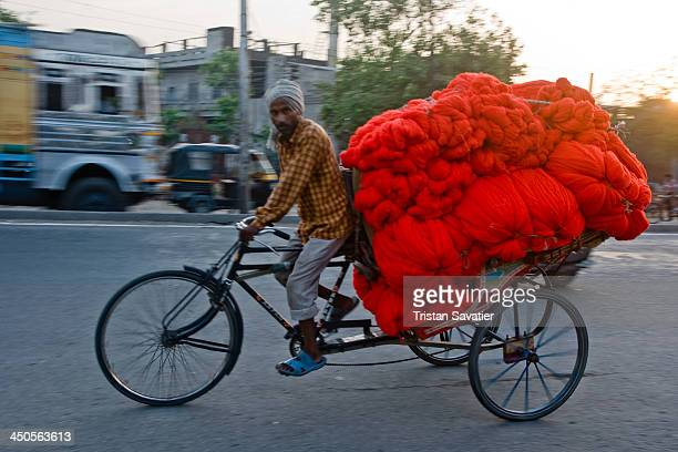 CONTENT] Cycle rickshaw with a big load of red wool Tricycle cargo freight man worker riding street road transporting Human interest bulk