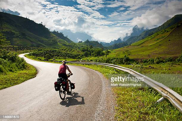 Cycle tourist rides road in Laos