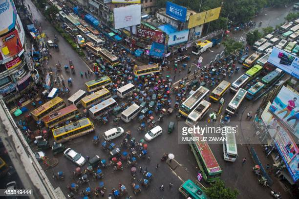 Cyclerickshaws and buses ply a street amid traffic during a nationwide strike called by the JamaateIslami in Dhaka on September 21 2014 The...