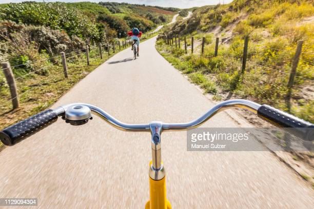 cycling along rural road between dunes near den haag, personal perspective,  scheveningen, south holland, netherlands - hollande méridionale photos et images de collection