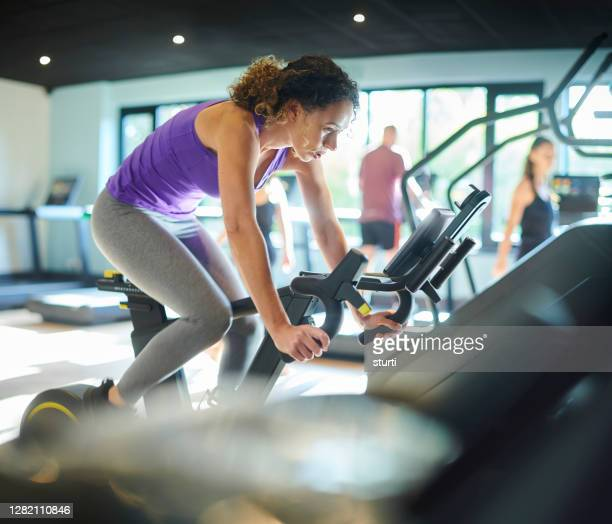 cycling at the gym - peloton stock pictures, royalty-free photos & images