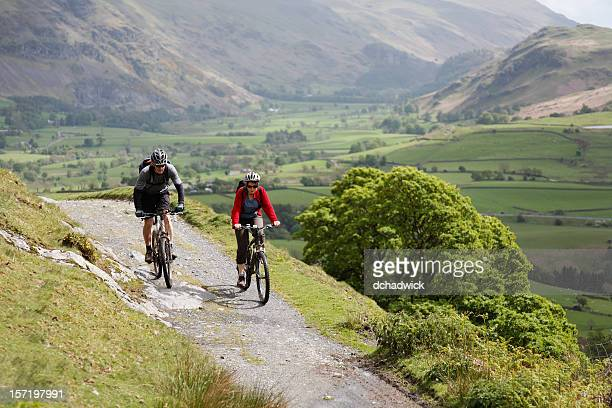 cycling couple - lake district stockfoto's en -beelden