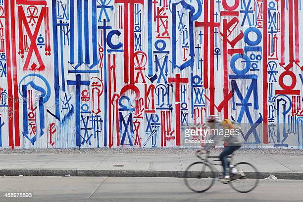 NYC cycling down Houston St past RETNA street art mural