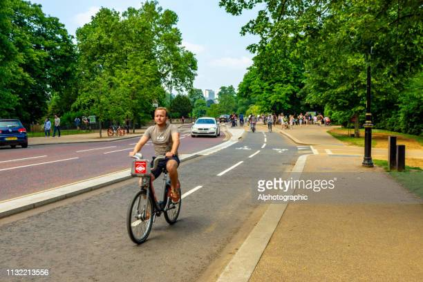cycling down the mall on a sunny day, in the centre of london, england - barclays cycle hire stock pictures, royalty-free photos & images