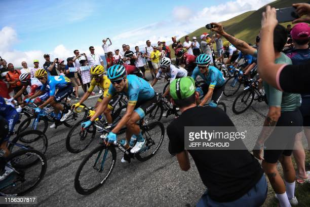 Cycling enthusiasts cheer France's Julian Alaphilippe , wearing the overall leader's yellow jersey, Denmark's Magnus Nielsen and cyclists in a curve...