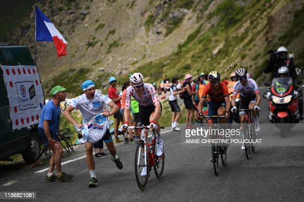 Cycling enthusiasts runs past Belgium's Tim Wellens wearing the best climber's polka dot jersey during the fourteenth stage of the 106th edition of...