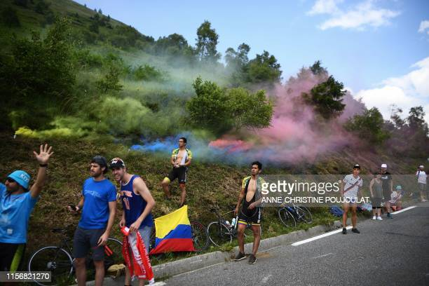 TOPSHOT Cycling enthusiasts wait for riders on the roadside as coloured smoke billows during the fourteenth stage of the 106th edition of the Tour de...