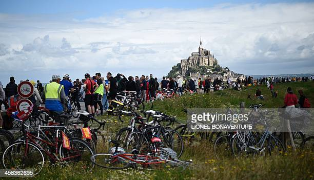Cycling fans gather near the start line prior to the 188 km first stage of the 103rd edition of the Tour de France cycling race on July 2, 2016...