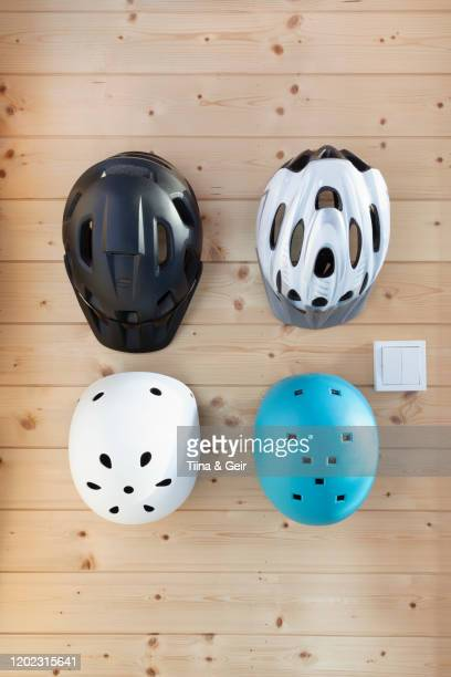 cycling helmets for adults and children hanging on wooden wall - cycling helmet stock pictures, royalty-free photos & images