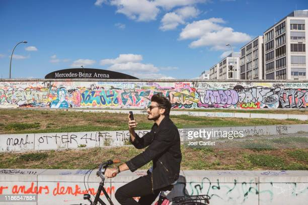 cycling in berlin at the east side gallery berlin wall - mercedes benz arena berlin stock pictures, royalty-free photos & images