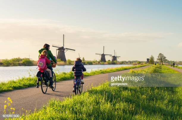 cycling past windmills at kinderdijk in holland - netherlands stock pictures, royalty-free photos & images
