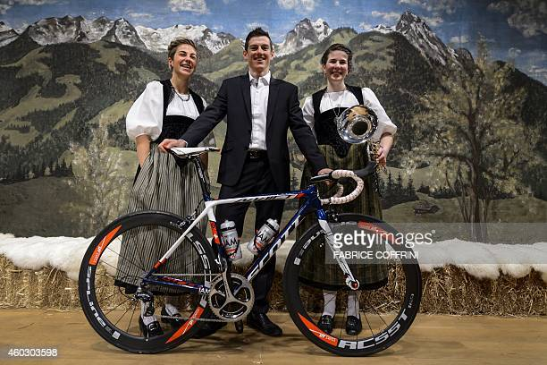 Cycling racer and leader of Swiss team IAM Mathias Frank of Switzerland poses between two woman wearing traditionnal dress during the presentation of...