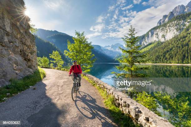 cycling senior at gosausee with dachstein view - european alps - upper austria stock pictures, royalty-free photos & images