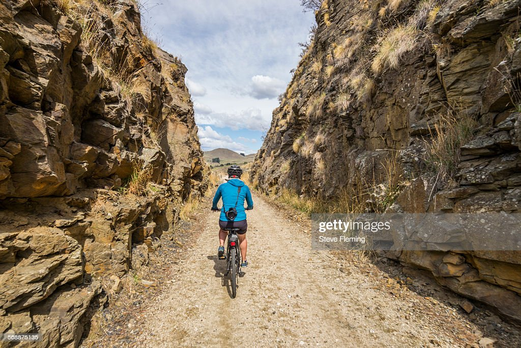 Cycling through a cutting on Otago Rail Trail. : Stock Photo