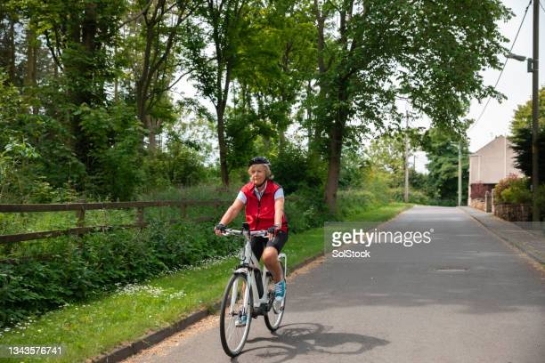 cycling through a village - morpeth stock pictures, royalty-free photos & images